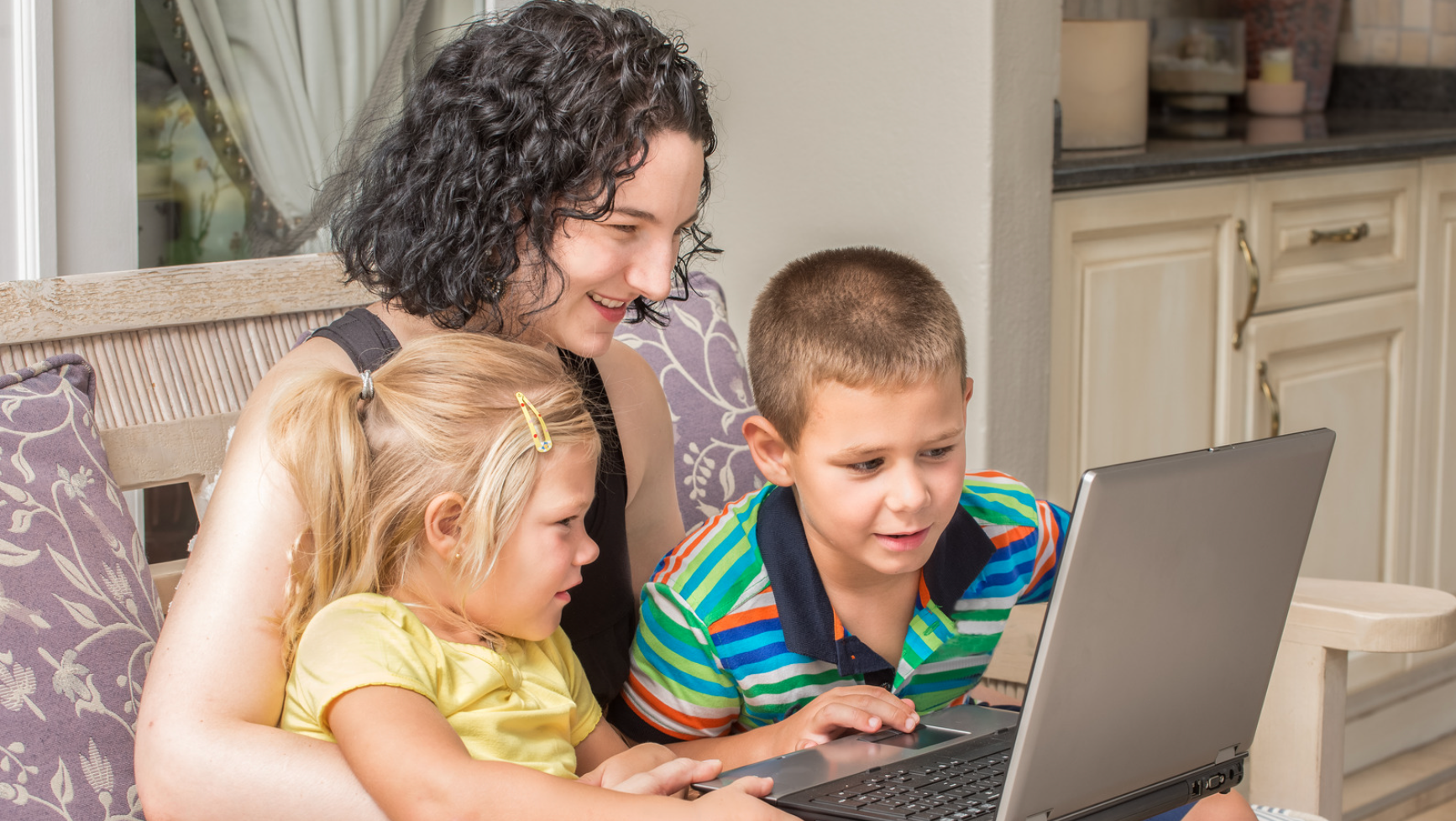 kids with their mother looking at laptop